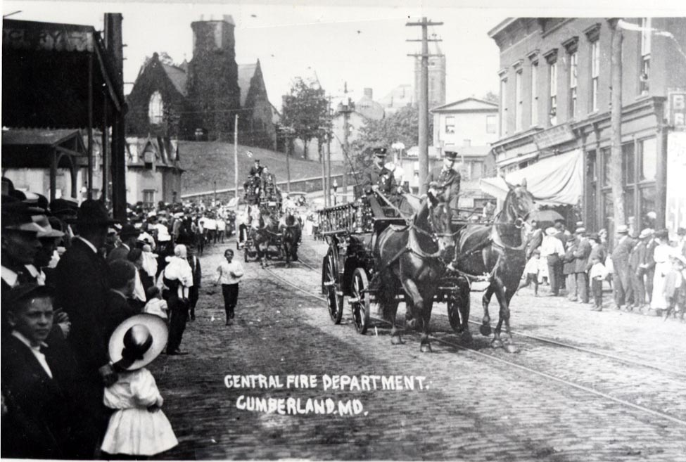 A black and white image of a horse-drawn fire wagon carrying several firefighters