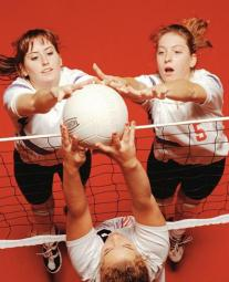 Three girls jumping to hit a volleyball during a volleyball game